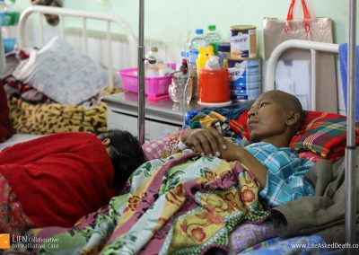 Recharging - an exhausted caregiver takes a rest alongside the patient in Yangon General Hospital, Myanmar.